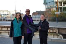 A London Northwestern Railway revenue protection officer and West Midlands Railway driver handing over old uniforms to Justin Frost from The Salvation Army Trading Company at Birmingham Snow Hill station.