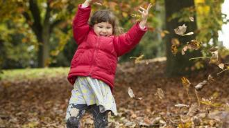 A child plays with leaves next to a deciduous tree in a wooded area in Wakefield, Yorkshire