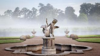 Cherub in the garden with the River Sow and mist in June on the Shugborough Estate, Staffordshire