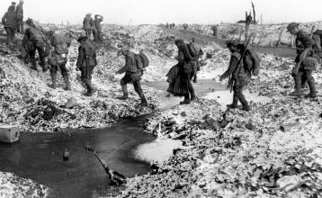 British soldiers negotiating a shell-cratered, Winter landscape along the River Somme in late 1916 after the close of the Allied offensive